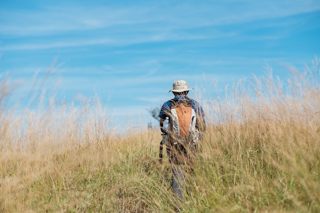 Молодой человек, стоящий в травянистом поле яркое голубое небо.
