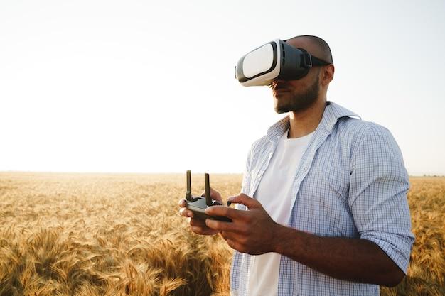 Молодой человек, стоящий в пшеничном поле на закате в очках виртуальной реальности