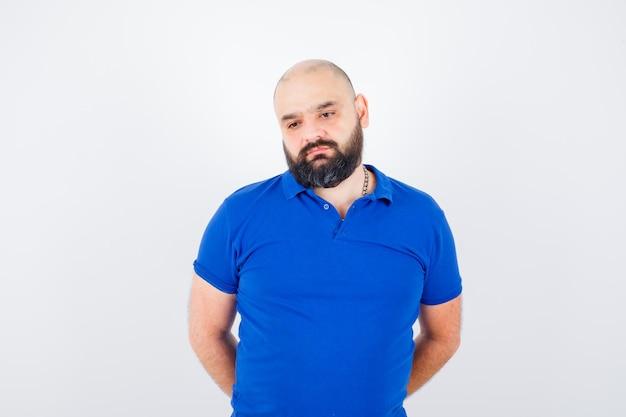 青いシャツに立って物思いにふける若い男。正面図。
