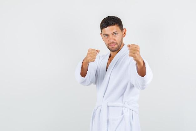 ボクサーのポーズで立っている若い男は白いバスローブを着て、パワフルな正面図を探しています。