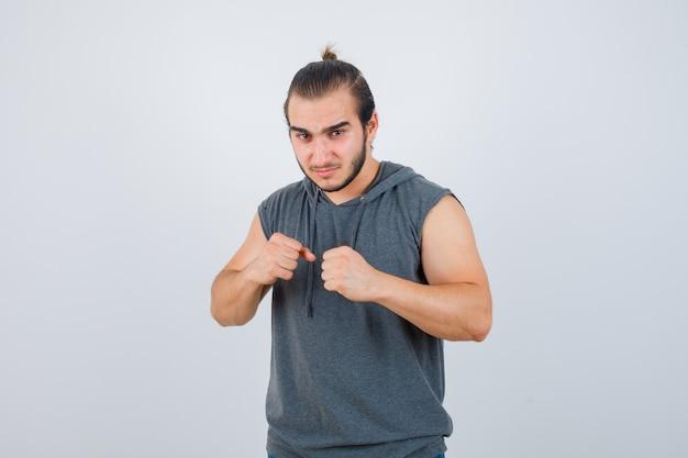 ノースリーブのパーカーで戦いのポーズで立っている若い男と自信を持って見えます。正面図。