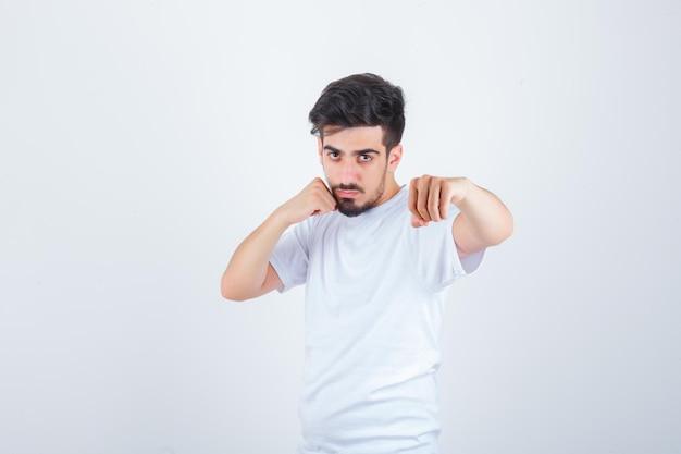 Молодой человек стоит в боевой позе в белой футболке и выглядит уверенно