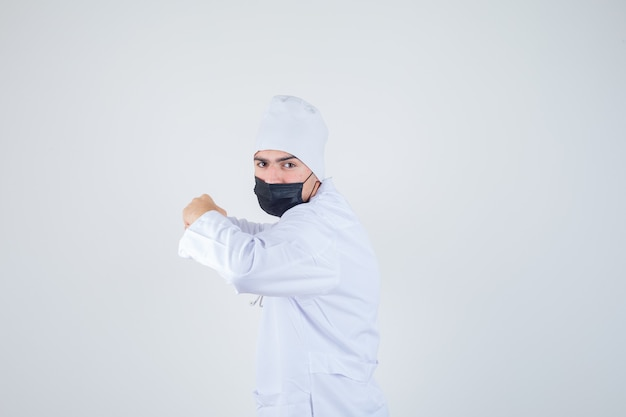 白い制服を着た戦闘ポーズで立っている若い男、マスクと決意を探しています。 。