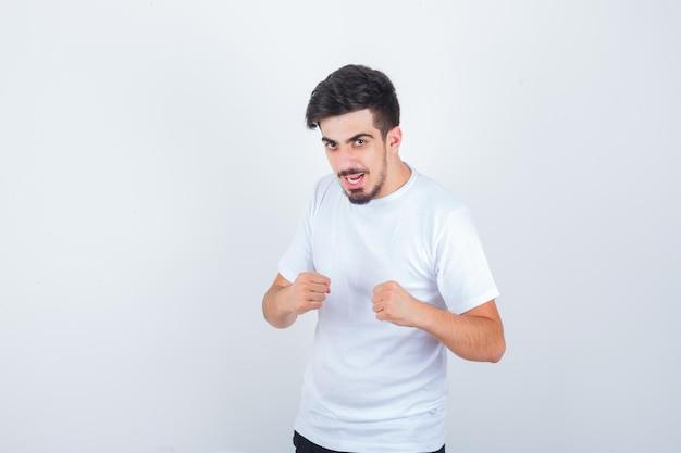 戦いのポーズで立っている若い男はtシャツでポーズをとって、意地悪に見えます