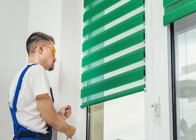 Молодой человек, стоящий перед ярким окном в комнате, регулирует зеленые жалюзи, занавески, белые