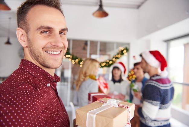 クリスマスプレゼントとカメラの前に立っている若い男