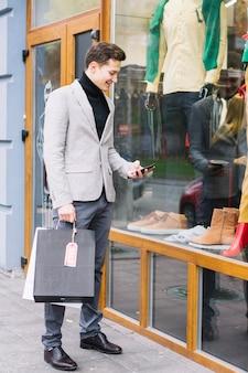Молодой человек, стоящий перед магазином с помощью смартфона