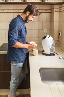 コーヒーを準備するキッチンに立っている若い男