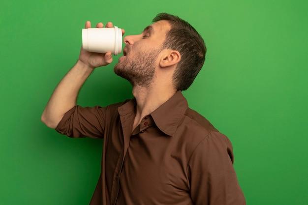 녹색 벽에 절연 플라스틱 커피 컵에서 커피를 마시는 프로필보기에 서있는 젊은 남자
