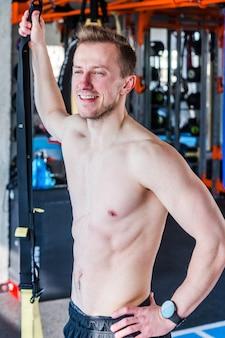 Молодой человек, стоящий в тренажерном зале. атлетическая модель фитнеса культуриста позирует после упражнений. вертикальное фото