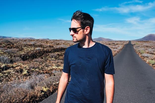 Молодой человек, стоящий посреди пустынной дороги в солнечный день.