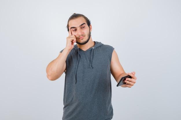 思考ポーズで立っている若い男、フード付きのtシャツで携帯電話を手に持って、賢明な正面図を探しています。