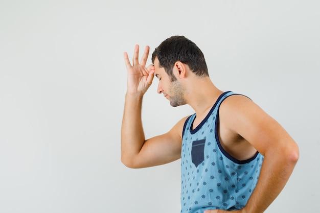 Молодой человек, стоящий в позе мышления в синей майке.