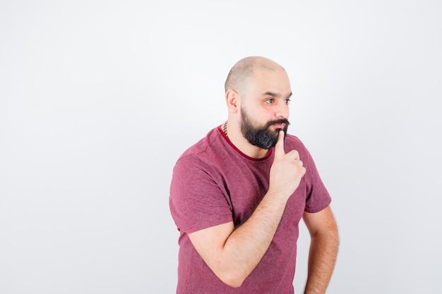Молодой человек, стоящий в позе мышления в розовой футболке и задумчивый. передний план.