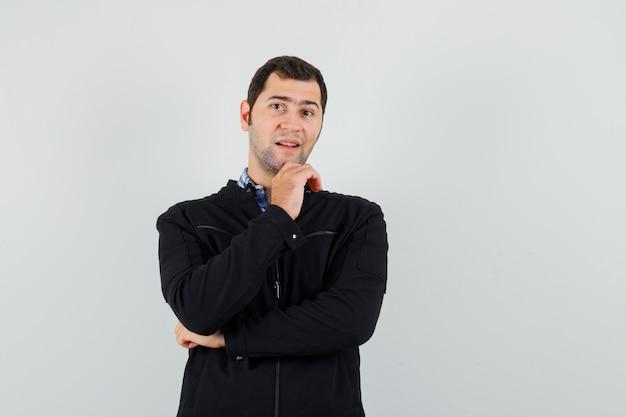 Молодой человек стоял в позе мышления в рубашке, куртке и выглядел оптимистично, вид спереди.