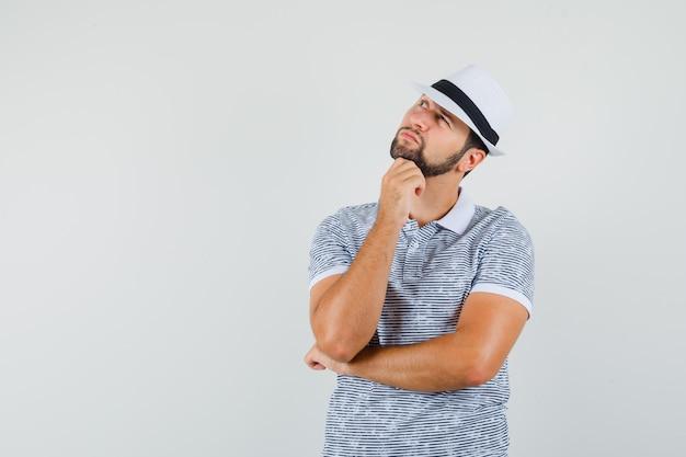 스트라이프 t- 셔츠, 모자에 생각 포즈에 서있는 젊은 남자가 생각 하 고, 전면보기를 찾고. 텍스트를위한 공간