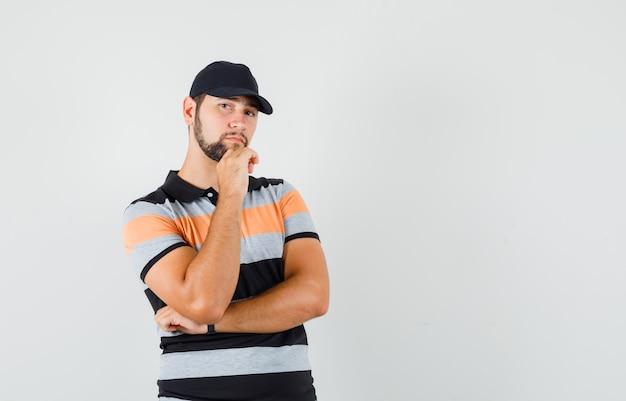 T- 셔츠, 모자에 생각 포즈에 서 있고 현명한 찾고 젊은 남자