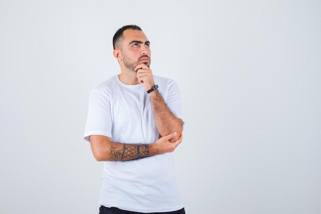 Молодой человек, стоящий в задумчивой позе в белой футболке и черных штанах, задумчиво выглядит