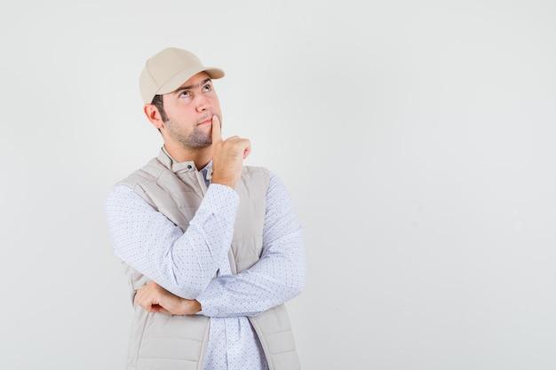 생각 포즈에 서있는 젊은 남자, 멀리보고 베이지 색 재킷과 모자에 입에 검지 손가락을 넣고 잠겨있는, 전면보기를보고.