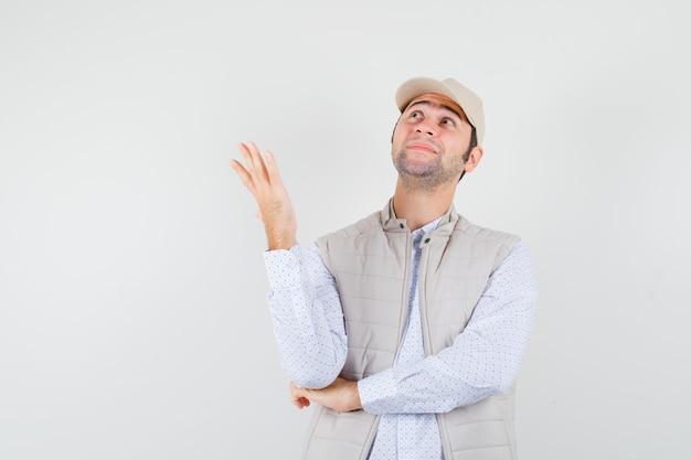 생각 포즈에 서있는 젊은 남자, 베이지 색 재킷과 모자를 멀리보고 행복, 전면보기를 찾고.