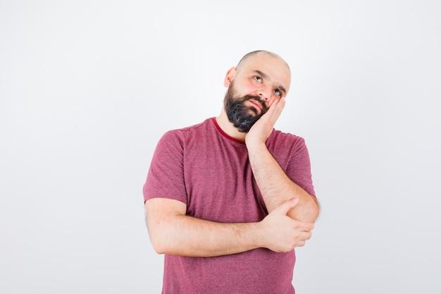 Молодой человек, стоящий в позе мышления, опираясь щекой на ладонь в розовой футболке и задумчиво, вид спереди.