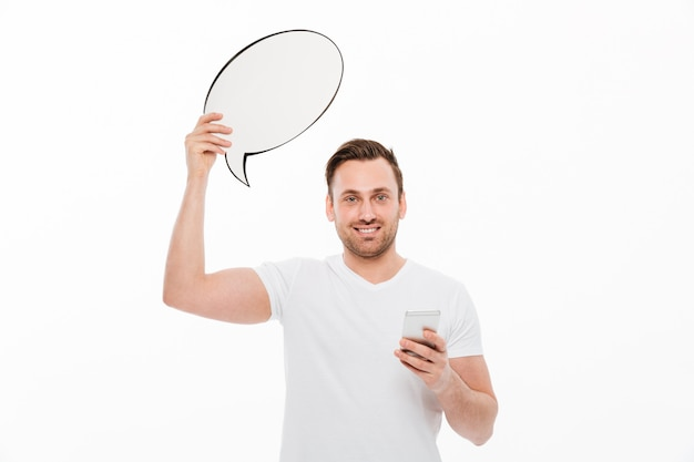 Young man standing isolated holding speech bubble