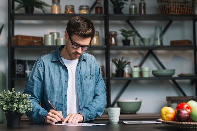 Young man standing behind the kitchen counter writing on paper with pencil