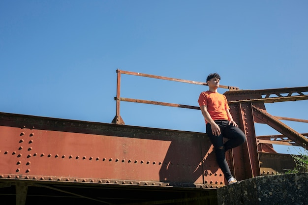 Young man standing on metallic bridge