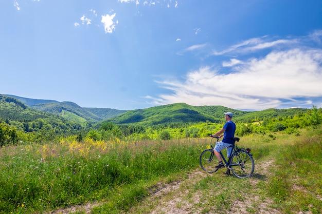 素晴らしい光線と穏やかな夏のアクティブな日の間に朝の霧で朝の日の出の自転車の近くに立っている若い男