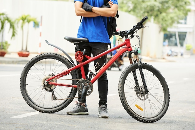 Young man standing near bicycle