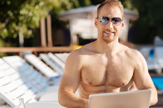 좋은 시간을 보내고 수영장 근처에 서있는 젊은 남자