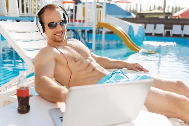 Молодой человек, стоящий возле бассейна, прекрасно проводит время