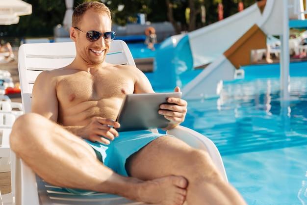 素晴らしい時間を過ごしているプールの近くに立っている若い男
