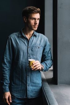 Young man standing near the window holding disposable coffee cup