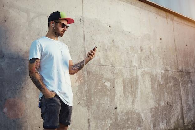 灰色のコンクリートの壁の横に立ってスマートフォンの画面を見て、白い耳栓で音楽を聴いている若い男