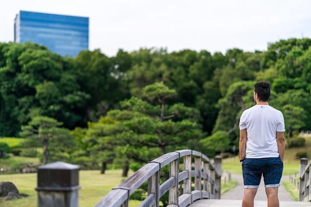 Молодой человек стоя на деревянном мосте в садах hama rikyu. токио, япония.