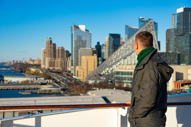 Молодой человек, стоящий на круизном лайнере и смотрящий на городской пейзаж нью-йорка. концепция счастливых каникул и путешествий.