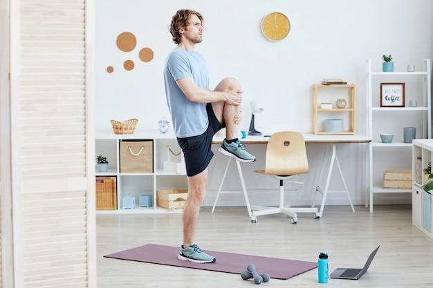 Молодой человек стоит на коврике и делает спортивные упражнения в комнате дома