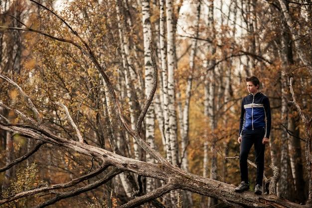 Молодой человек, стоящий на упавшем дереве