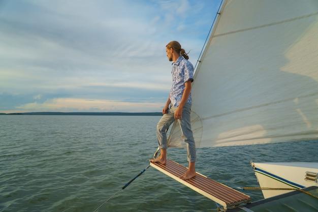 Молодой человек, стоящий на передней части яхты и глядя на море