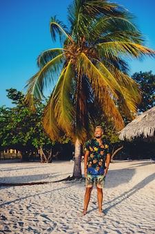 Молодой человек, стоящий на пляже, улыбаясь на фоне пальм