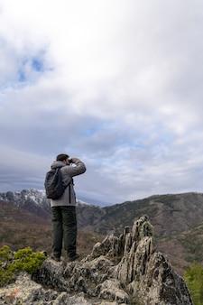 昼間で冬の山の崖の上に立っている若い男
