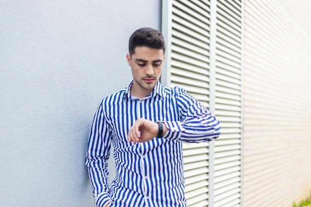 Молодой человек, стоя на улице, глядя наручные часы