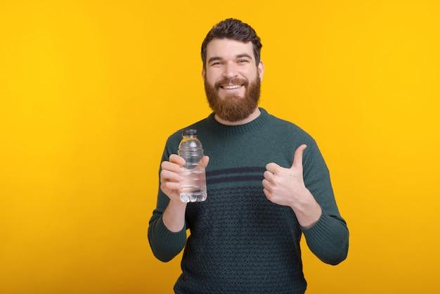 Молодой человек стоя над желтой предпосылкой и держа бутылку с водой и показывая большие пальцы руки вверх