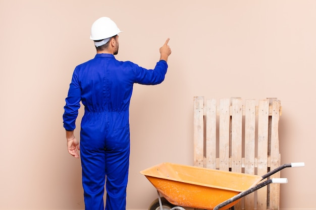 Young man standing and pointing to object on copy space, rear view construction concept