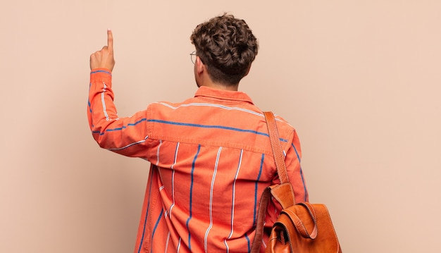 Young man standing and pointing to object on copy space, rear view. student concept