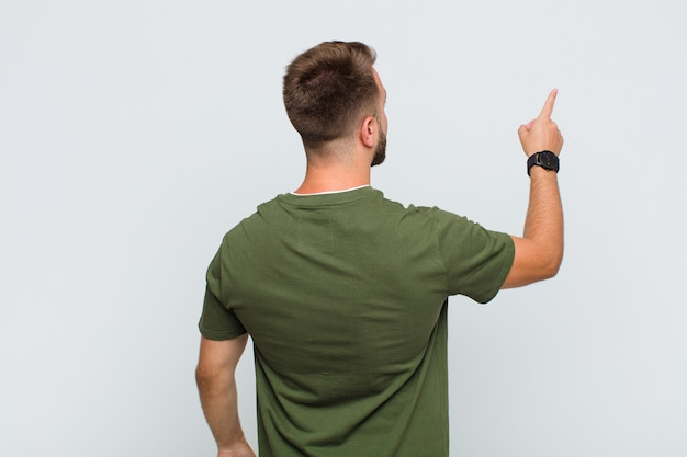 Young man standing and pointing to object on copy space, rear view