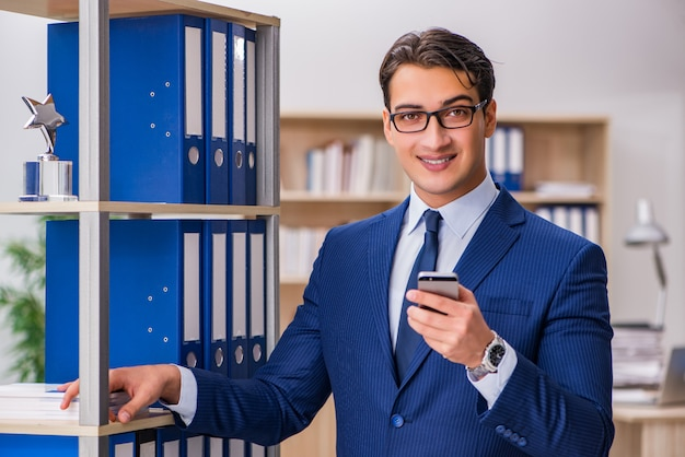 Young man standing next to the shelf with folders