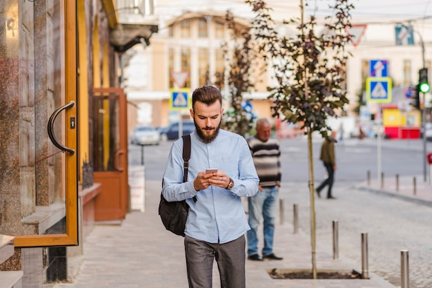 Young man standing on sidewalk using cellphone