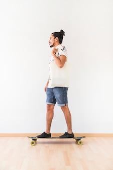 Young man standing on skatingboard over the hardwood floor